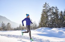Germany, Bavaria, Isar valley, Vorderriss, woman jogging in winter — Stock Photo