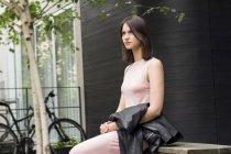 Retrato de mujer joven sentada en la banca y sosteniendo la chaqueta negra - foto de stock