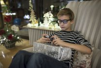 Boy paying with smartphone with present on lap — Stock Photo
