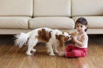 Дівчинка годує собака з файлом cookie, сидячи на підлозі у вітальні — стокове фото