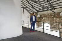 Homme d'affaires permanent dans loft Bureau — Photo de stock
