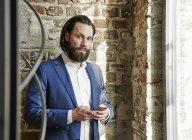 Homme d'affaires exploitation cellulaire — Photo de stock