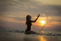 Surfeur femelle éclaboussures d'eau dans l'océan au coucher du soleil — Photo de stock