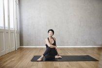 Frau praktizieren Yoga auf Holzboden — Stockfoto
