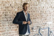 Businessman buttoning jacket in front of brick wall — Stock Photo