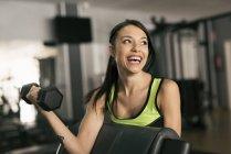 Giovane donna caucasica sportiva sollevamento pesi in palestra — Foto stock