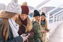 Gijn, Asturias, Spain, four young women using smartphones in city — Stock Photo