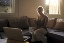 Blond woman sitting on the couch at backlit and using cell phone — Stock Photo