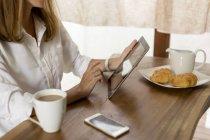 Donna che utilizza tablet a tavola per la colazione — Foto stock