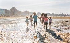 Grupo de niños jugando en la playa, Gijón, Asturias, España - foto de stock