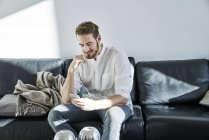 Smiling man sitting on couch looking at cell phone — Stock Photo