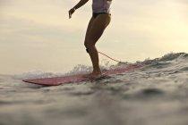 Indonesia, Bali, legs of woman on surfboard — Stock Photo
