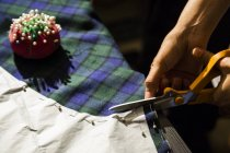 Close-up of woman cutting cloth with scissors — Stock Photo