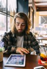 Stylish hipster man using digital tablet in coffee shop — Stock Photo