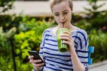 Retrato de jovem mulher bebendo smoothie e usando telefone celular — Fotografia de Stock