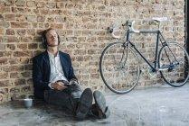 Розслабленої бізнесмен з навушниками, притулившись цегляна стіна — стокове фото