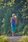 Germany, Bavaria, Young woman jogging at Lake Walchensee — Stock Photo