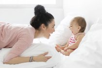Mother and baby playing on a white bed — Stock Photo