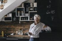 Портрет бізнесмен з смартфон і чашкою кави в кухні — стокове фото