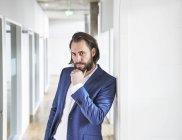 Uomo d'affari in piedi in edificio per uffici — Foto stock