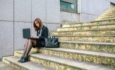 Donna d'affari seduto sulle scale e utilizzando il computer portatile — Foto stock
