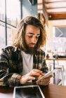 Stylish hipster man using smartphone in coffee shop — Stock Photo