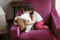 Toddler girl sitting on a chair hugging her dog — Stock Photo