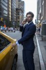 Businessman on phone entering yellow taxi — Stock Photo