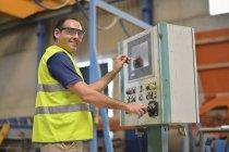 Pressionar o botão no painel de controle em fábrica de concreto trabalhador — Fotografia de Stock