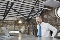 Businessman with laptop sitting at table — Stock Photo