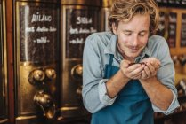 Coffee roaster smelling coffee beans in shop — Stock Photo