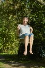 Smiling young woman sitting on swing — Stock Photo