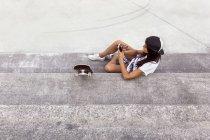 Gijn, Asturie, Spagna, skateboarder girl invia messaggi con il suo smartphone — Foto stock
