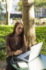 Joven empresaria trabajando en el parque de la ciudad sentada con el ordenador portátil a la mesa en sol - foto de stock