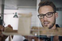 Portrait of pensive businessman holding architectural model — Stock Photo