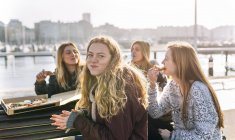 Vier junge Frauen, die Mittagessen Pizza im freien — Stockfoto
