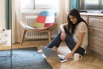 Молодая женщина сидит на полу дома и использует ноутбук — стоковое фото