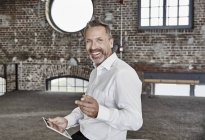 Businessman with tablet standing in loft — Stock Photo