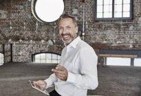 Geschäftsmann mit Tablet stehen im loft — Stockfoto