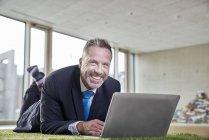 Uomo d'affari che si trova sul tappeto erboso sintetico con il computer portatile — Foto stock