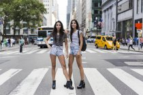 Soeurs jumelles, debout sur le passage clouté — Photo de stock