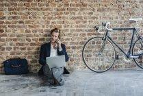 Бізнесмен, сидячи на підлозі і використання ноутбука з мобільного телефону — стокове фото