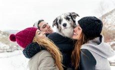 Leon, Espanha, três amigos se divertindo com seu cachorro na neve — Fotografia de Stock