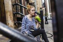 Портрет молодої жінки, сидячи на сходах з зеленим льстец — стокове фото