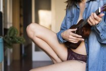 Mid section of young woman playing ukulele guitar — Stock Photo