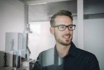 Retrato de sonriente hombre de negocios en la oficina mirando a un lado - foto de stock