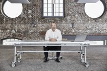 Businessman sitting at rolling table — Stock Photo