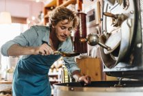 Kaffeeröster im Geschäft untersucht Kaffeebohnen — Stockfoto