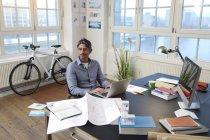 Людина, використовуючи ноутбук бюро в сучасні офісні — стокове фото