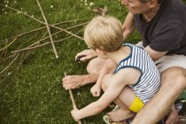 Man and boy cutting twigs on lawn with a pocketknife — Stock Photo